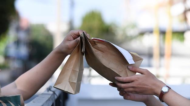 집 문앞에서 고객에게 음식이 담긴 종이 봉지를 주는 배달원의 모습을 가까이서 보세요.