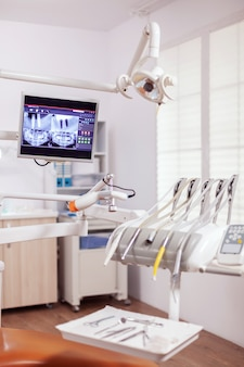 歯科医の歯科用ツールとプロの椅子の拡大図。誰も入っていない口腔病学用キャビネットと、口腔治療用のオレンジ色の器具。