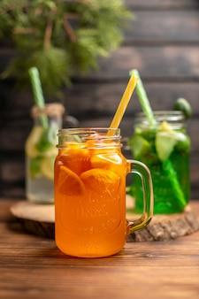 Крупным планом вид детокс-воды и свежего сока в бутылках с трубками на коричневом деревянном фоне