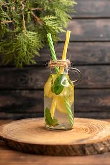 갈색 나무 배경에 레몬과 민트로 만든 해독 물보기를 닫습니다