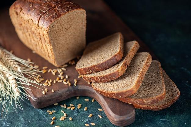 青の暗い色の背景に木製まな板の上の食餌療法の黒いパンのスパイク小麦のビューをクローズアップ