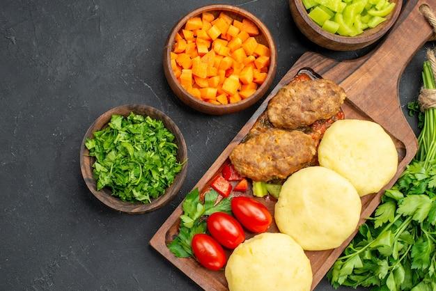 暗闇の中でおいしいカツレツ野菜と緑と夕食のクローズアップビュー
