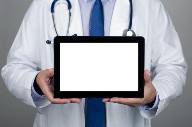 Закройте вверх по взгляду доктора в белом халате со стетоскопом показывая пустой цифровой пк таблетки. copyspace