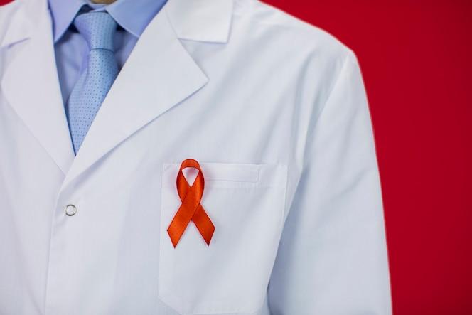 それの赤いhivエイズリボンと白い医療コートで医師のクローズアップ表示