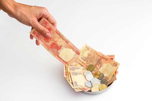 흰색 바탕에 인도 지폐와 동전이 있는 기부 접시의 보기를 닫습니다.