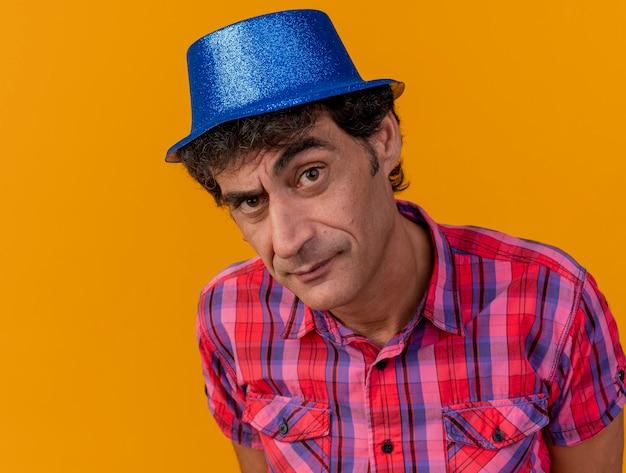 복사 공간 오렌지 배경에 고립 된 카메라를보고 파티 모자를 쓰고 의심스러운 중년 백인 파티 남자의 근접 촬영보기