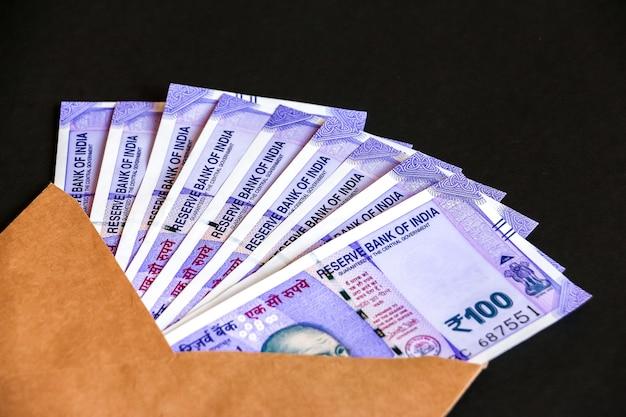 真新しいインドの100ルピー紙幣で封筒のクローズアップビュー。