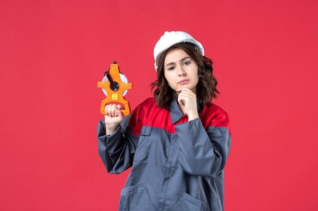 측정 테이프를 표시하고 붉은 벽에 깊이 생각하는 하드 모자와 제복을 입은 여성 건축가의보기를 닫습니다