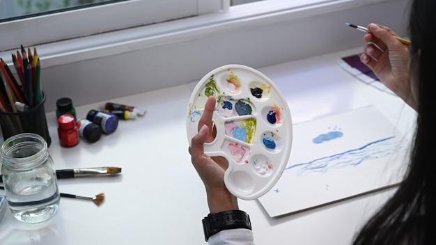 彼女のワークショップで作業しているカラーパレットとペイントブラシを保持している女性アーティストのクローズアップビュー。