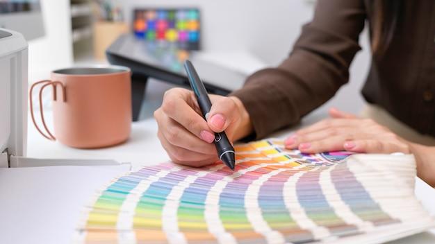 사무실 방에서 컴퓨터 책상에 색상 견본에 색상을 선택하는 여성 디자이너의보기를 닫습니다