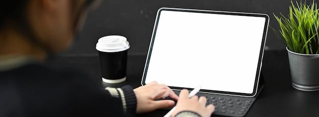黒いテーブルにデジタルタブレットで入力する女性フリーランサーのクローズアップ表示