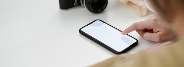 목업 스마트 폰을 사용하여 휴식을 취하는 여성 프리랜서의 뷰를 닫습니다
