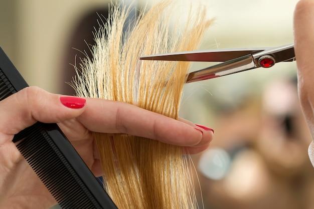 髪の毛の先端を切る女性の美容師の手のクローズアップビュー。ケラチン修復、健康な髪、最新のヘアファッショントレンド、ヘアカットスタイルの変更、スプリットエンドの短縮、楽器店のコンセプト