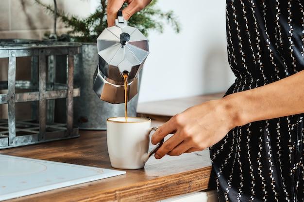 Крупным планом зрения женская рука наливает кофе
