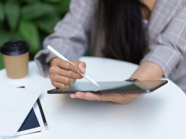 Крупным планом вид женской руки с помощью цифрового планшета на журнальном столике с ноутбуком и напитком