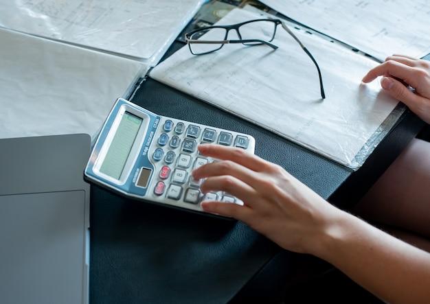 計算を行う女性の手のクローズアップビューとオフィスデスク作業プロセスオフィスコンセプトにメガネをかけたドキュメント
