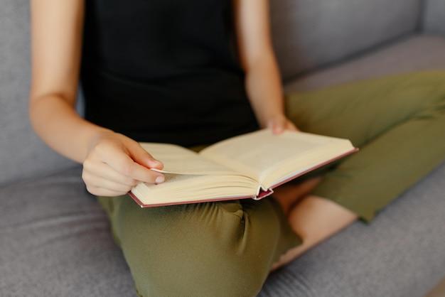 本を読んで、本のページをめくる女性の手のクローズアップビュー。趣味のコンセプトです。家に。