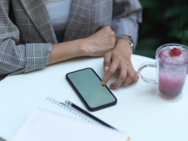 Крупным планом вид женских рук, трогающих смартфон на журнальном столике с напитком и ноутбуком в кафе