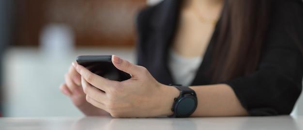 事務室のテーブルでスマートフォンを使用して女性の手のビューをクローズアップ