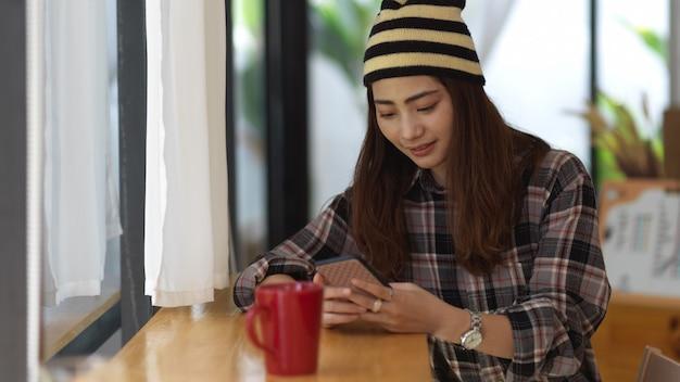 커피 머그잔과 나무 테이블에 스마트 폰을 사용하여 여성 손보기를 닫습니다