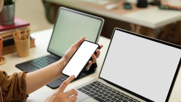 Крупным планом вид женских рук, использующих смартфон, сидя за офисным столом с двумя ноутбуками