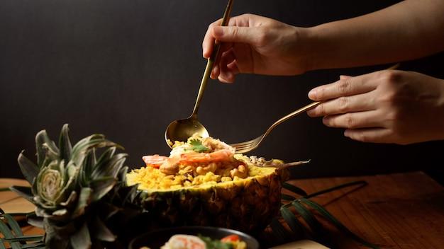 Крупным планом вид женских рук со столовыми приборами, едящими жареный рис с ананасом (kao pad sapparod)