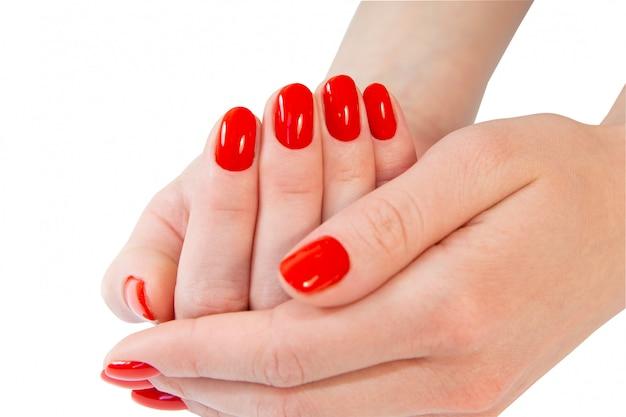 Крупным планом вид женских рук с красным маникюром.