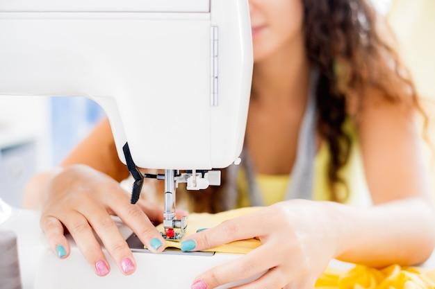 Крупным планом вид женских рук, работающих на швейной машине