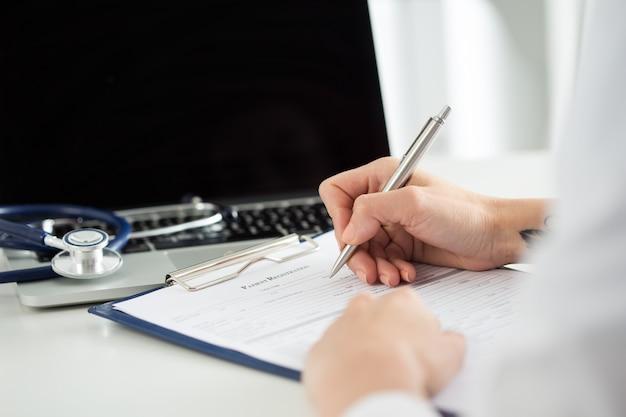 Крупным планом вид рук врачей женской медицины, заполняющих медицинскую форму пациента