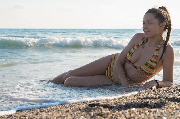 들어오는 파도에 다리와 모래 해변에 앉아 여성의 보기를 닫습니다. 여름 휴가 개념입니다.