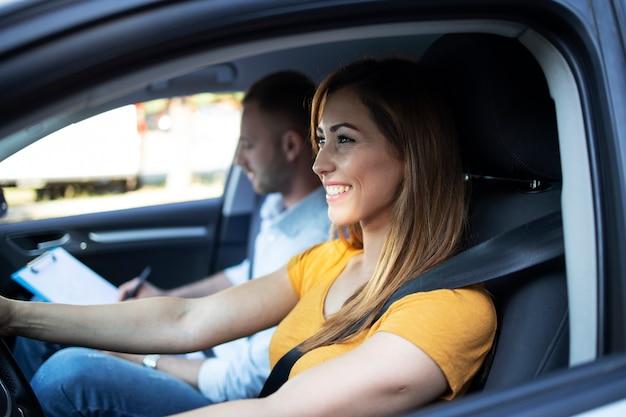 체크리스트를 들고 자동차와 강사를 운전하는 여성 학생의보기를 닫습니다