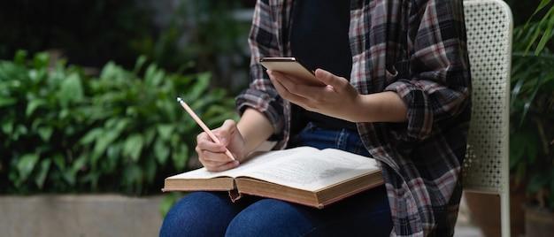 Крупным планом вид студентки, читающей книгу и использующей смартфон, сидя в саду