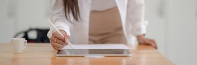 スタイラスペンでデジタルタブレットに書く女子大生のクローズアップ表示