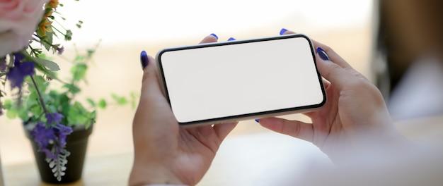 コーヒーショップで水平型スマートフォンを使用して女性のクローズアップ表示