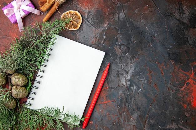 モミの枝の紫色のギフトと赤い背景に閉じたスパイラルノートブックシナモンライムのクローズアップビュー
