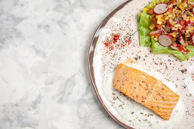 空きスペースのある染色された白い表面の皿に魚の食事とおいしいサラダの接写
