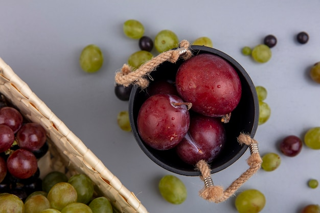 Крупным планом вид ароматных королевских плюотов в миске с виноградом в корзине и виноградными ягодами на сером фоне