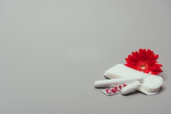 Close up view of flower,pills, menstrual pads and tampons