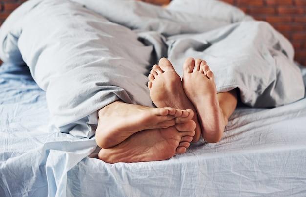 Крупным планом вид стопы пары, которая вместе спит в спальне в утреннее время.