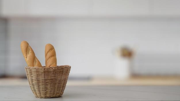 Закройте вверх по взгляду французской корзины багета и скопируйте космос на мраморном столе с запачканной комнатой кухни