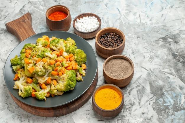 흰색 테이블에 나무 커팅 보드에 신선하고 건강한 야채 샐러드의 뷰를 닫습니다