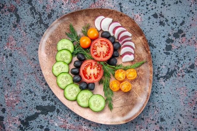 混合色の背景に茶色のプレートで新鮮なみじん切り野菜のビューをクローズアップ