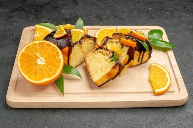 Крупным планом вид свежих апельсиновых дольок и нарезанных ломтиков торта на темном столе