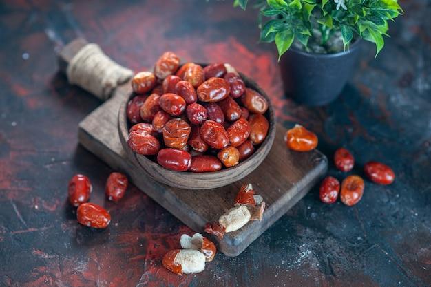 木製のまな板とミックスカラーの背景に植木鉢のボウルに新鮮な生のグミの果実のクローズアップビュー