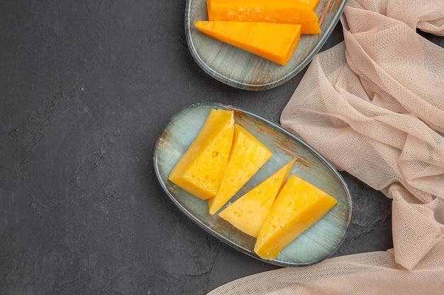 검정색 배경에 수건에 신선한 맛있는 치즈 조각의 뷰를 닫습니다