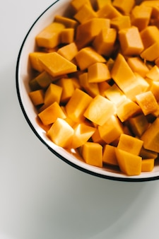 白いプレートに新鮮で鮮やかなオレンジ色のカボチャの部分のクローズアップビュー。
