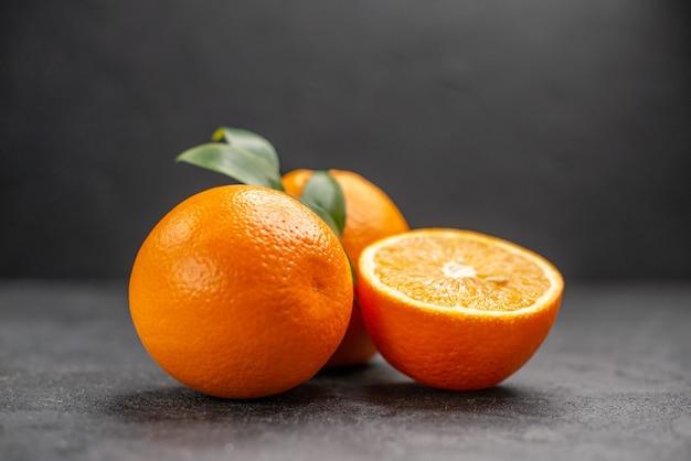 暗いテーブルの上の新鮮な丸ごとスライスしたレモンのクローズアップビュー