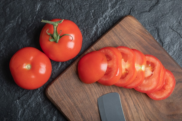 Крупным планом вид свежесобранных, сочных помидоров на темном каменном фоне. фото высокого качества