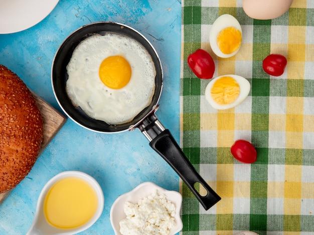 Крупным планом вид жареного яйца в сковороде с помидорами яйцо сливочное масло на синем