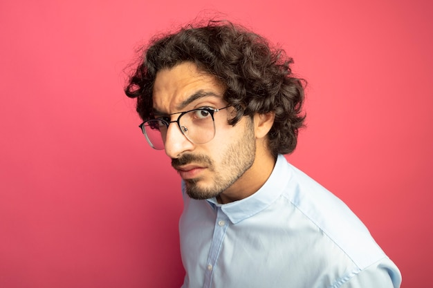 분홍색 벽에 고립 된 전면을보고 프로필보기에 서 안경을 쓰고 인상을 찌푸리고 젊은 잘 생긴 남자의 근접 촬영보기